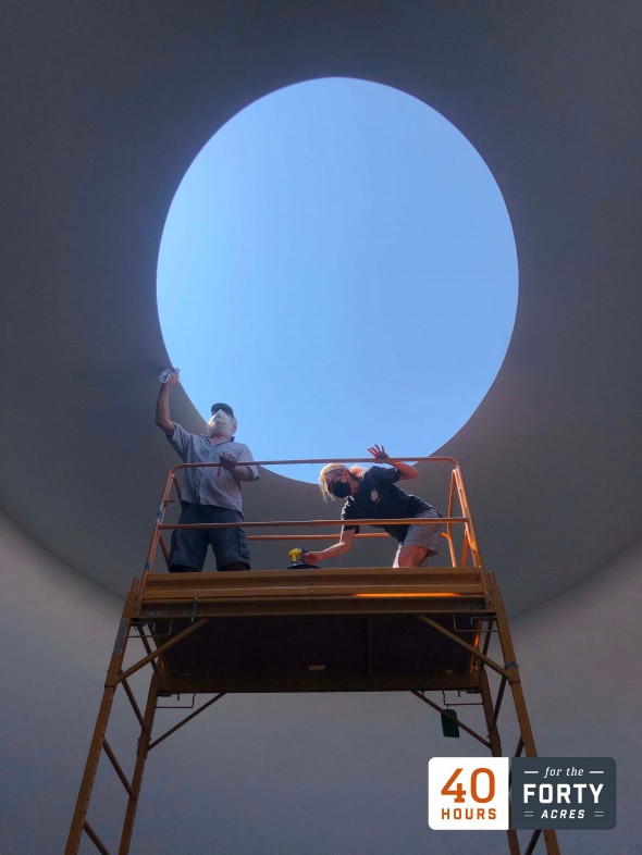 """Two people stand on a scaffold in James Turrell's skyspace """"The Color Inside"""" and they stand against the blue sky framed by the oculus."""