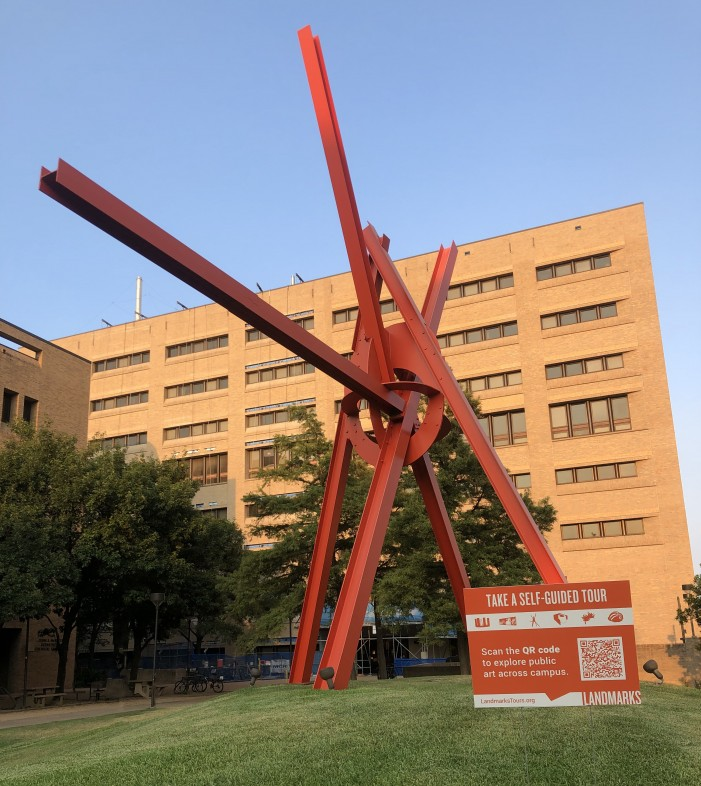 """A photo of Mark di Suvero's """"Clock Knot"""" with a yard sign with information about virtual tours"""