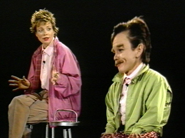 A woman on a stool looking at a person with a mustache