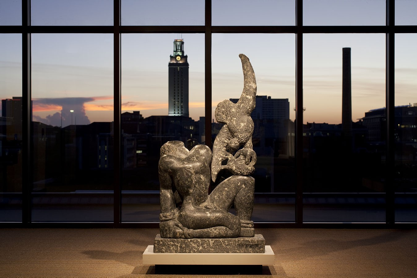A sculpture in front of a large window with a tower in the background
