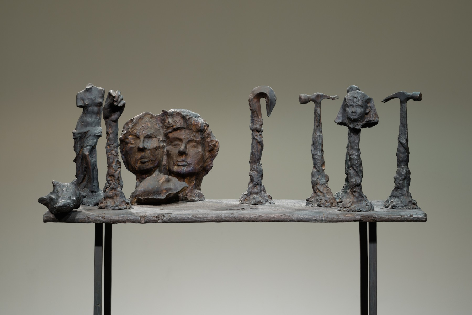 Figures of bodies, faces, and tools on a sculpture