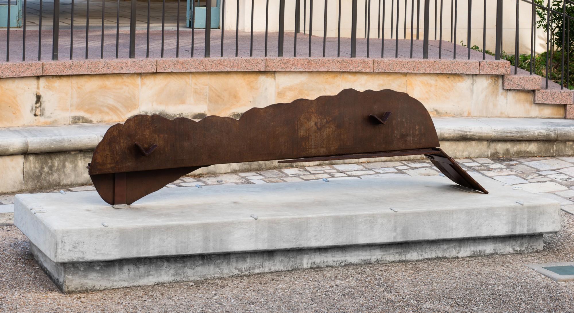 A brown sculpture on a concrete base
