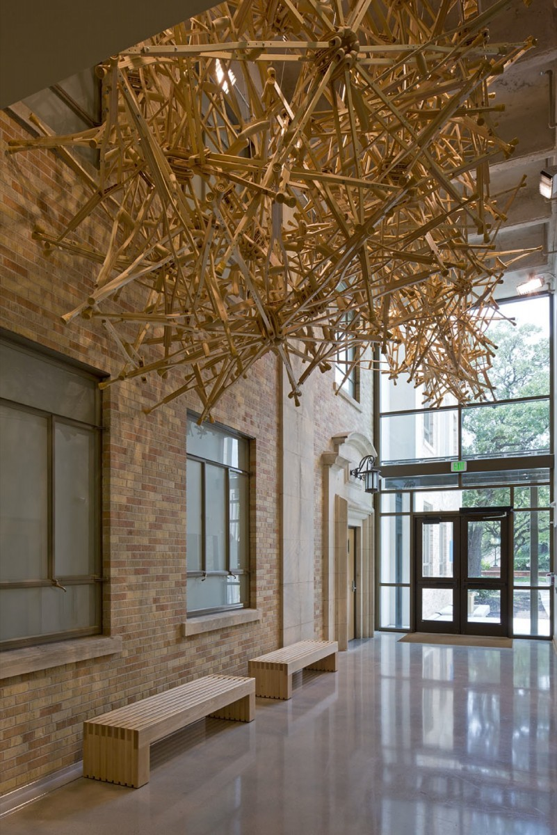 A hanging sculpture made out of wooden crutches