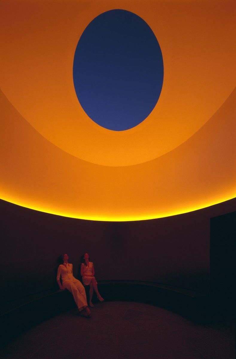 two people sitting in orange lit room