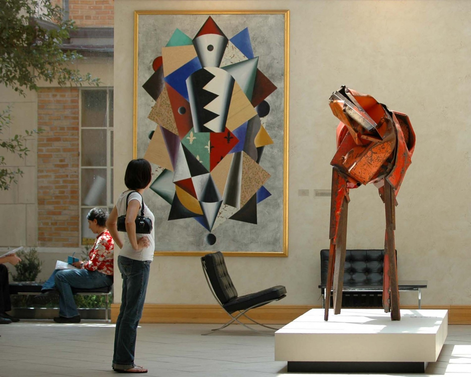 A person standing looking at a red horse sculpture indoors