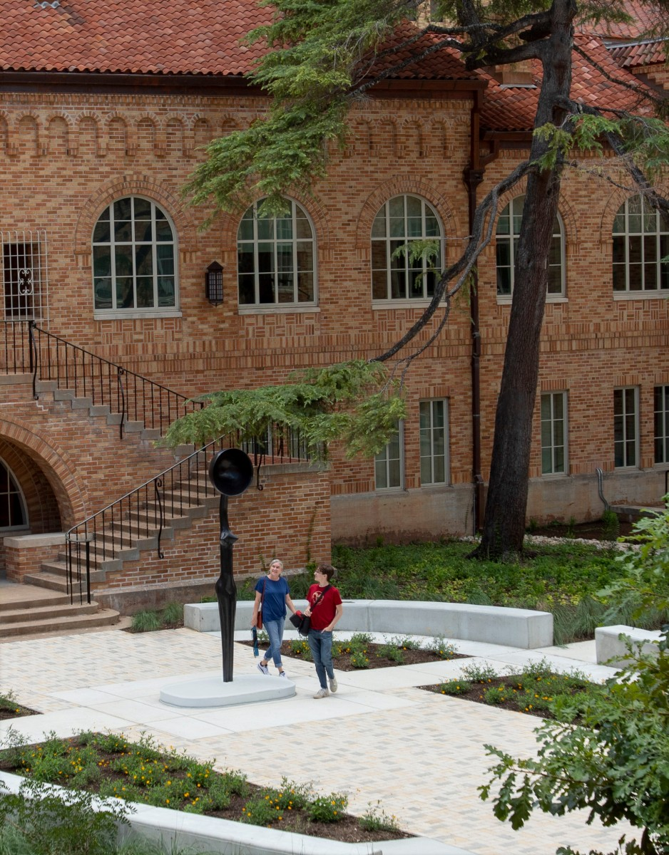 Two people seen from a high vantage point look at Simone Leigh's Sentinel IV, a tall slender figure with a bowlcrown in place of a head. They are surrounded by architecture and the landscaping of the space.
