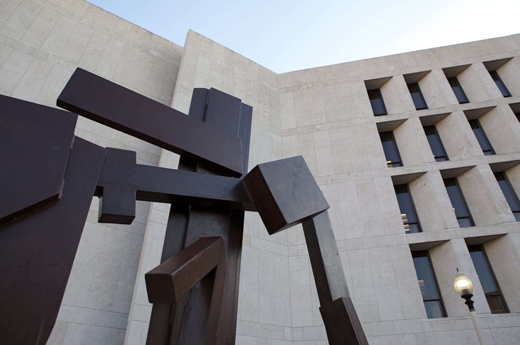 flat brown surface sculpture up against limestone building