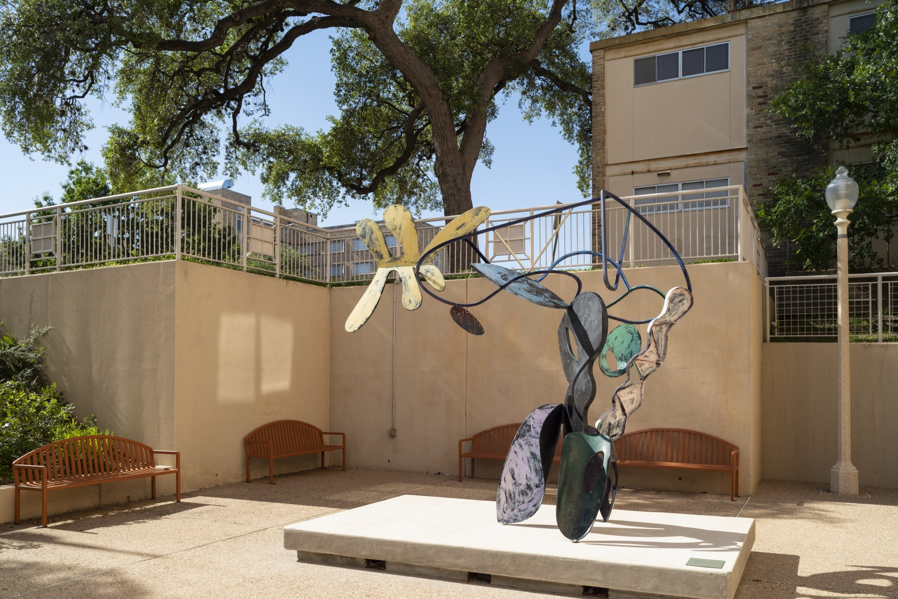 A large bendy sculpture with parts colored in different colors in a courtyard with benches surrounding it