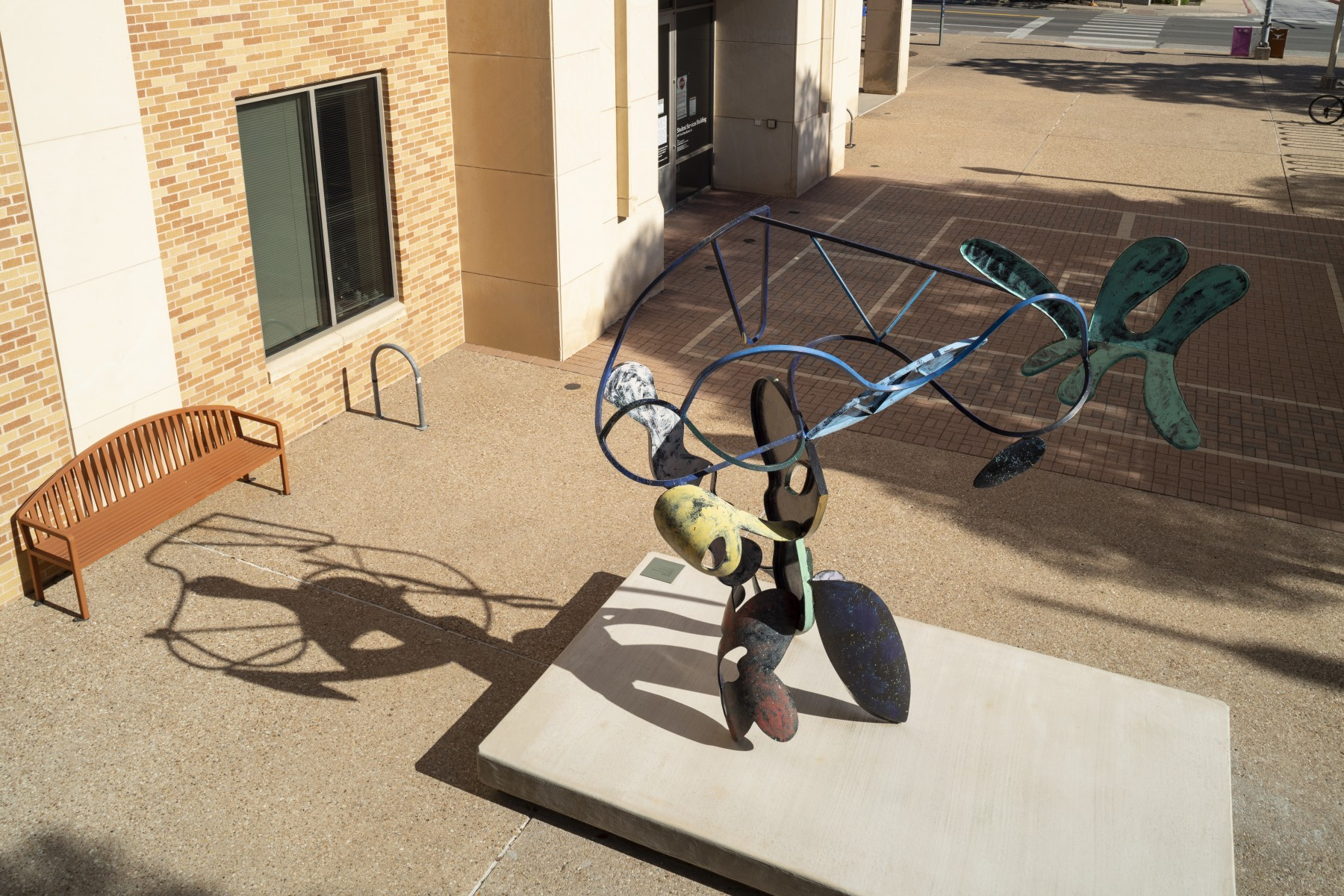 A large bendy sculpture with parts colored in different colors in a courtyard as seen from above