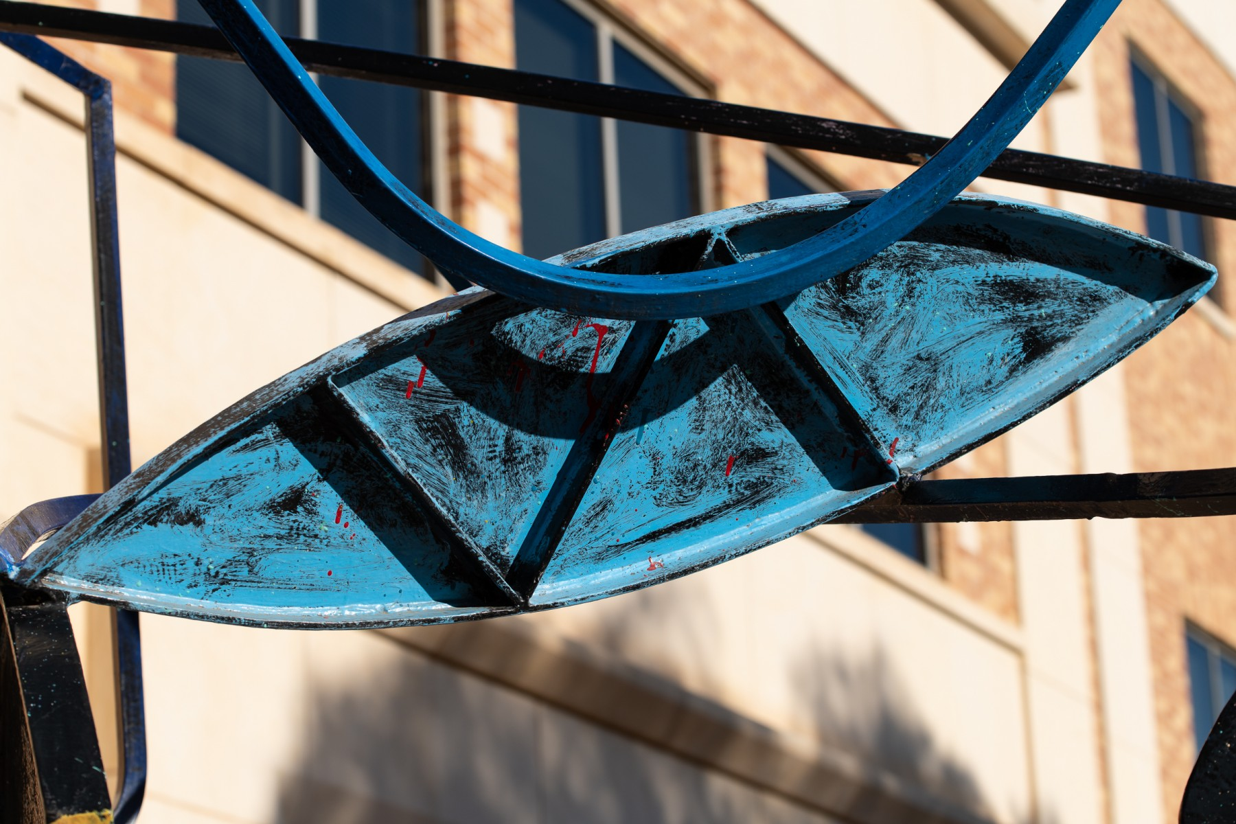 A detail of the sculpture that is almost almond shaped which streches across the whole image plane, a zigzag cuts across the shape which is painted blue.