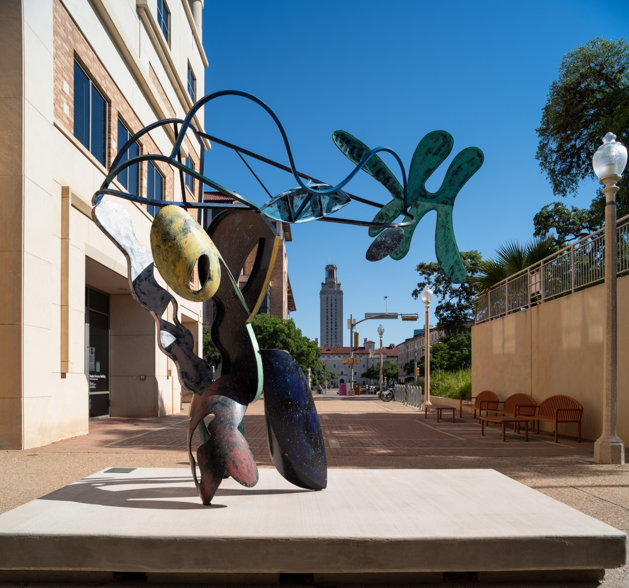 A large bendy sculpture with parts colored in different colors in a courtyard as seen from behind with the UT Tower framed by the sculpture