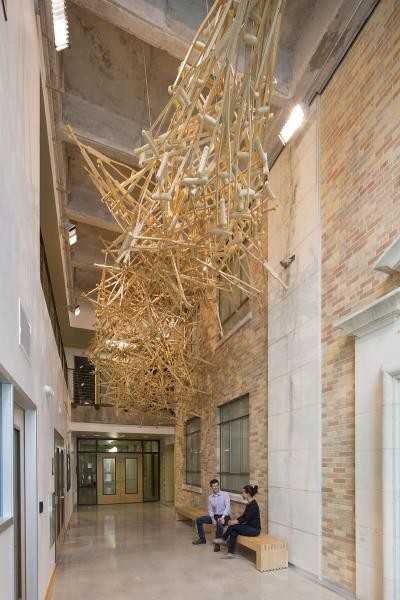 A hanging sculpture made out of wooden crutches with two people sitting underneath