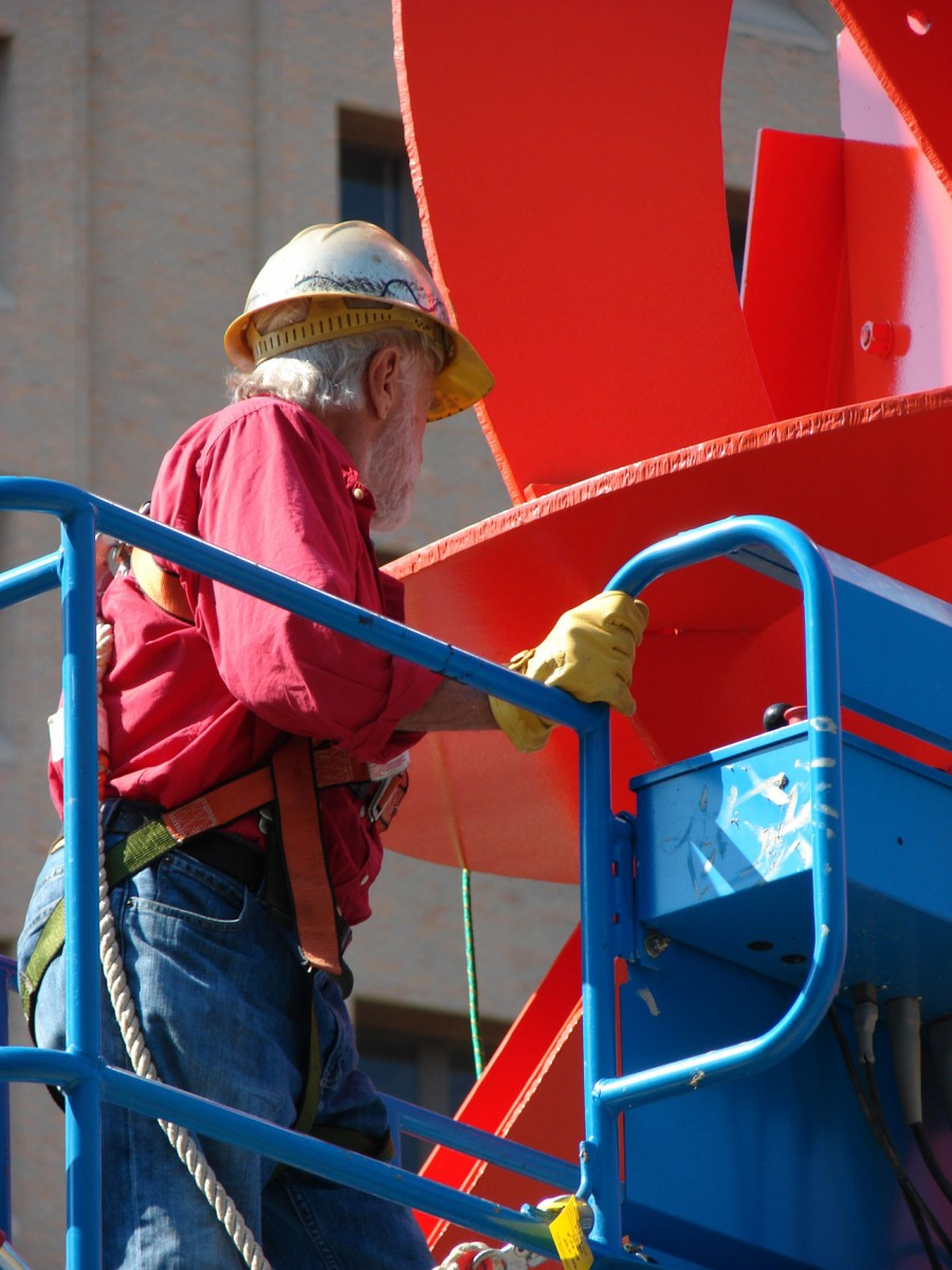 A man working on a large red metal sculpture