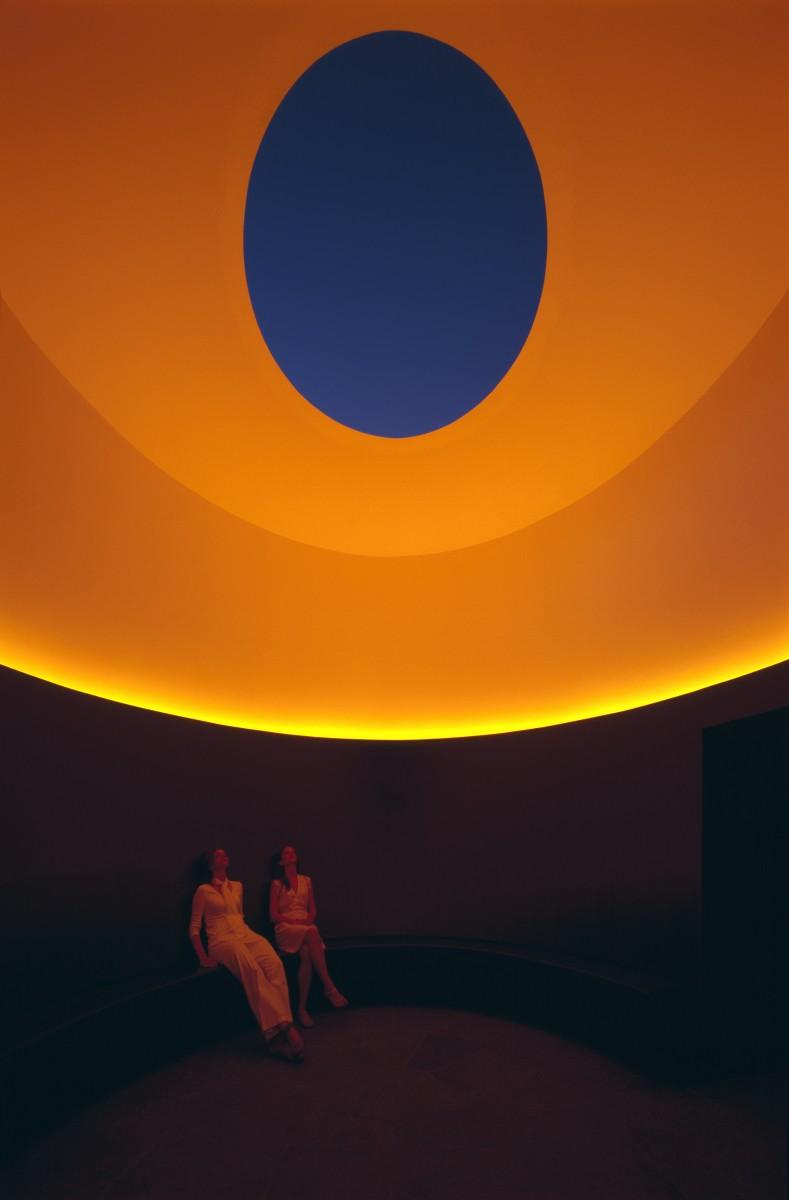 two people sitting in orange lit room