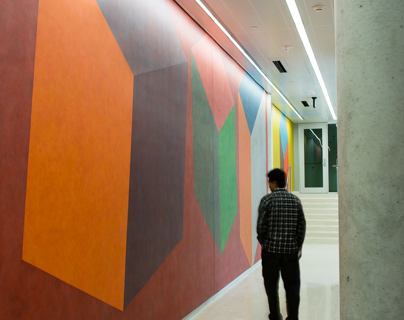 side view of person walking by colored wall