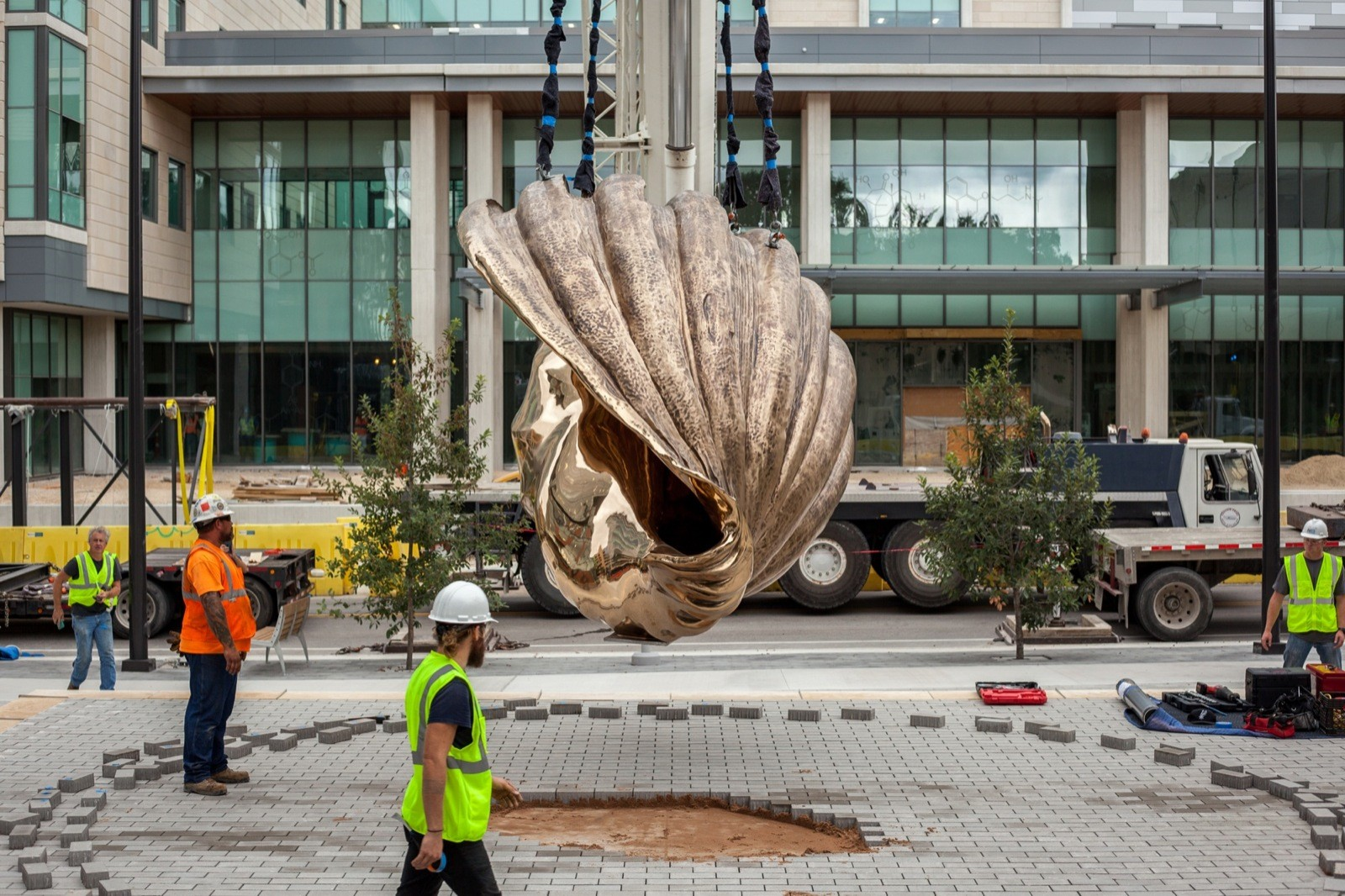 A bronze shell hanging from a crane