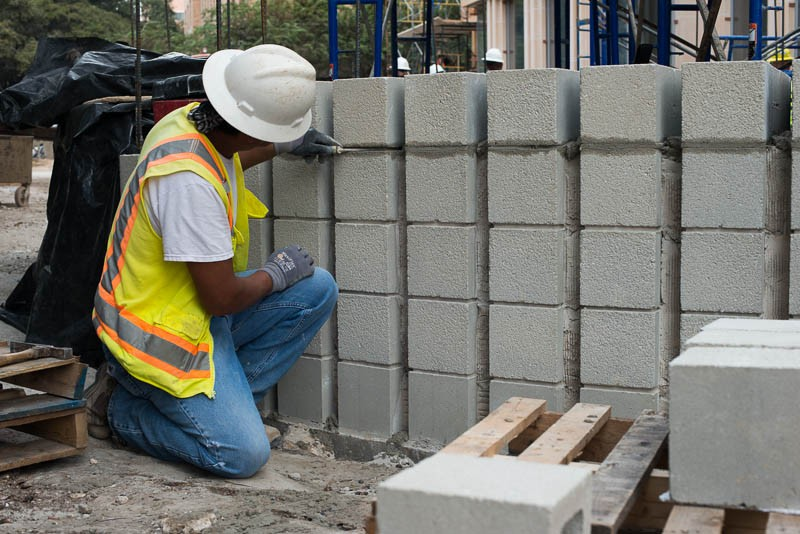 person leaning down touching bricks
