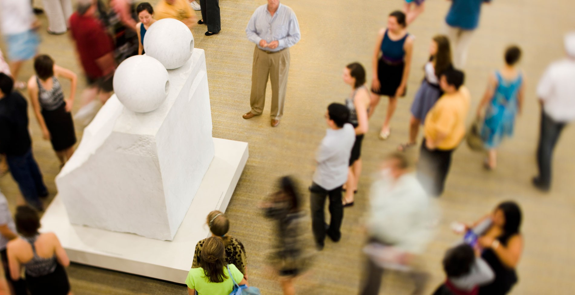 People standing around a large marble sculpture