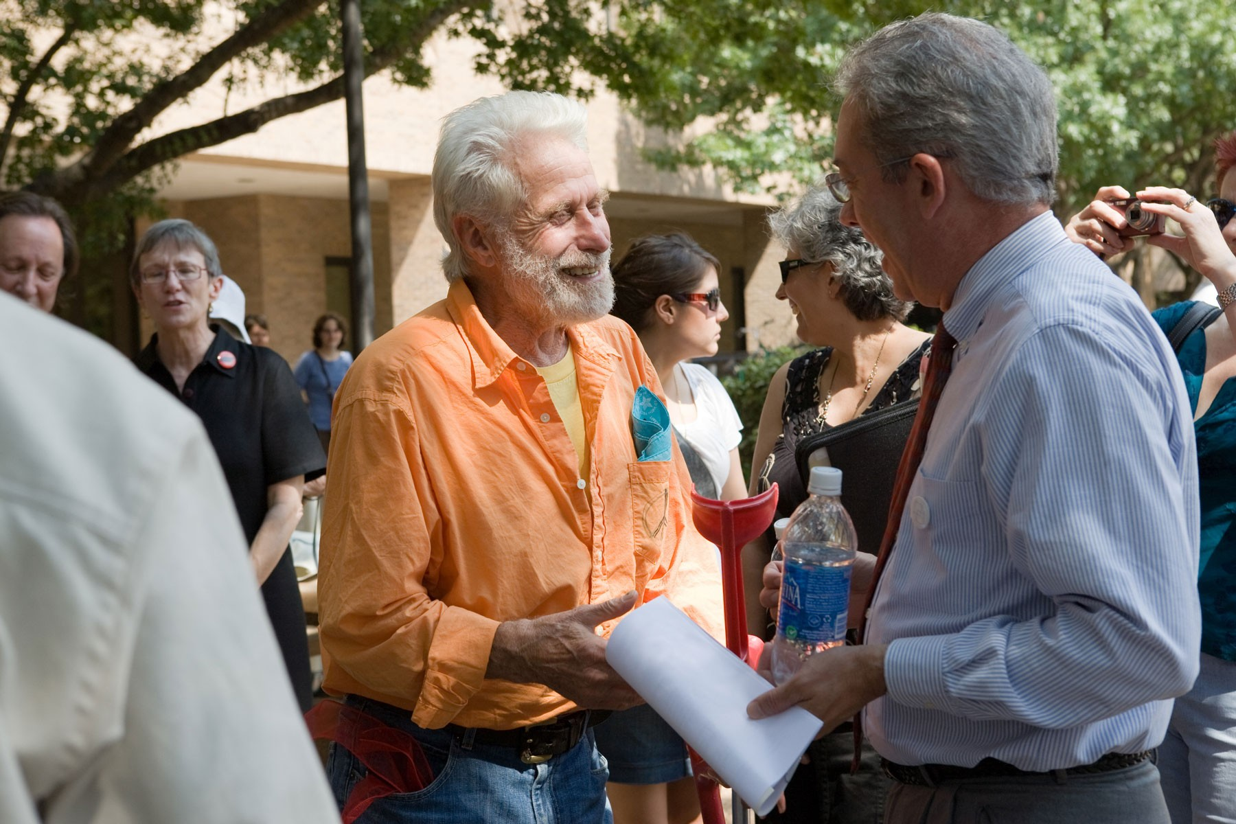 An older man talking to another man
