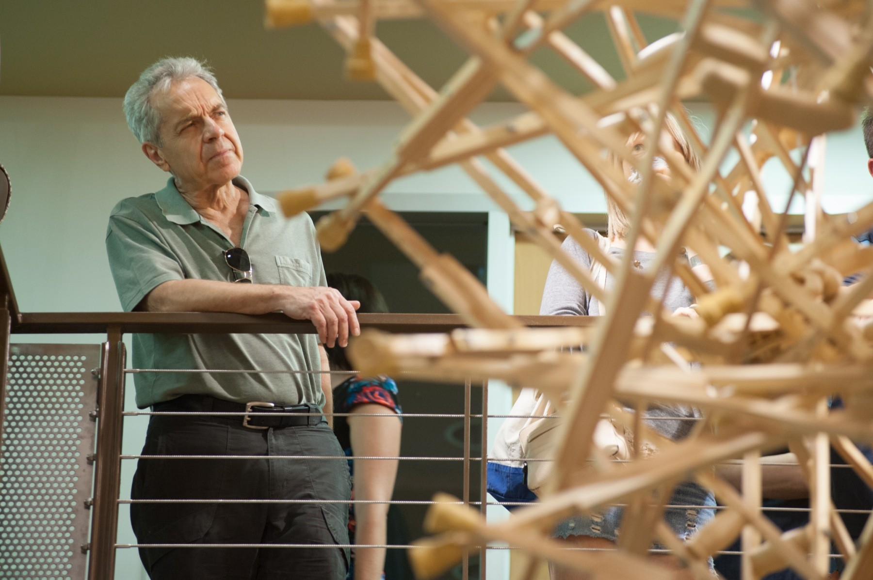 A man looking at a hanging sculpture made out of wooden crutches