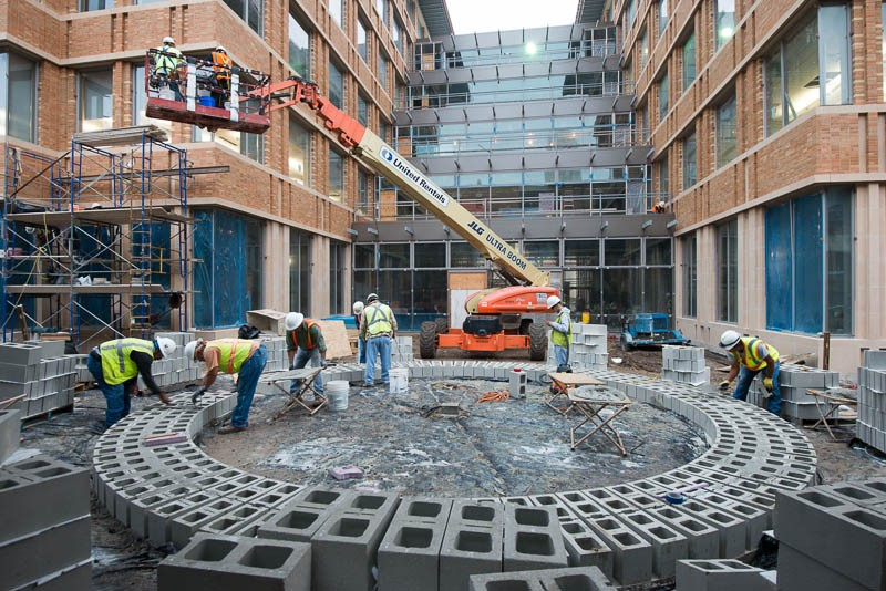 bricks in circular form with people leaning over different parts