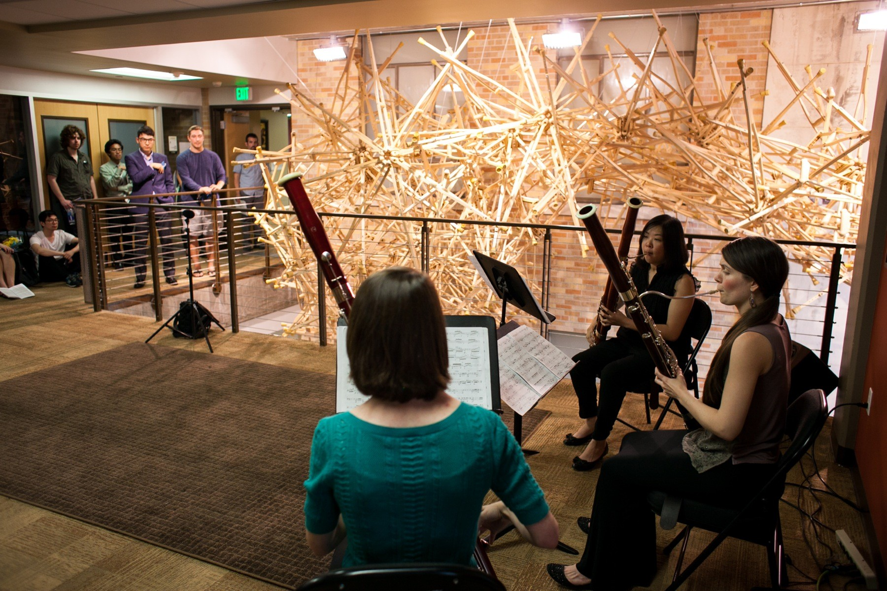 People performing with oboes next to a hanging sculpture made out of wooden crutches