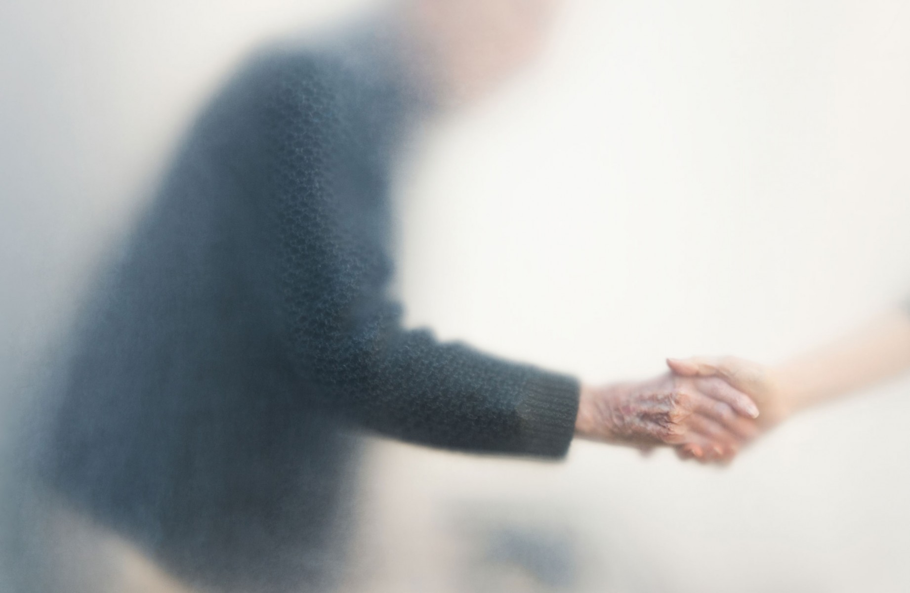 An older gentleman grabbing someone's hand