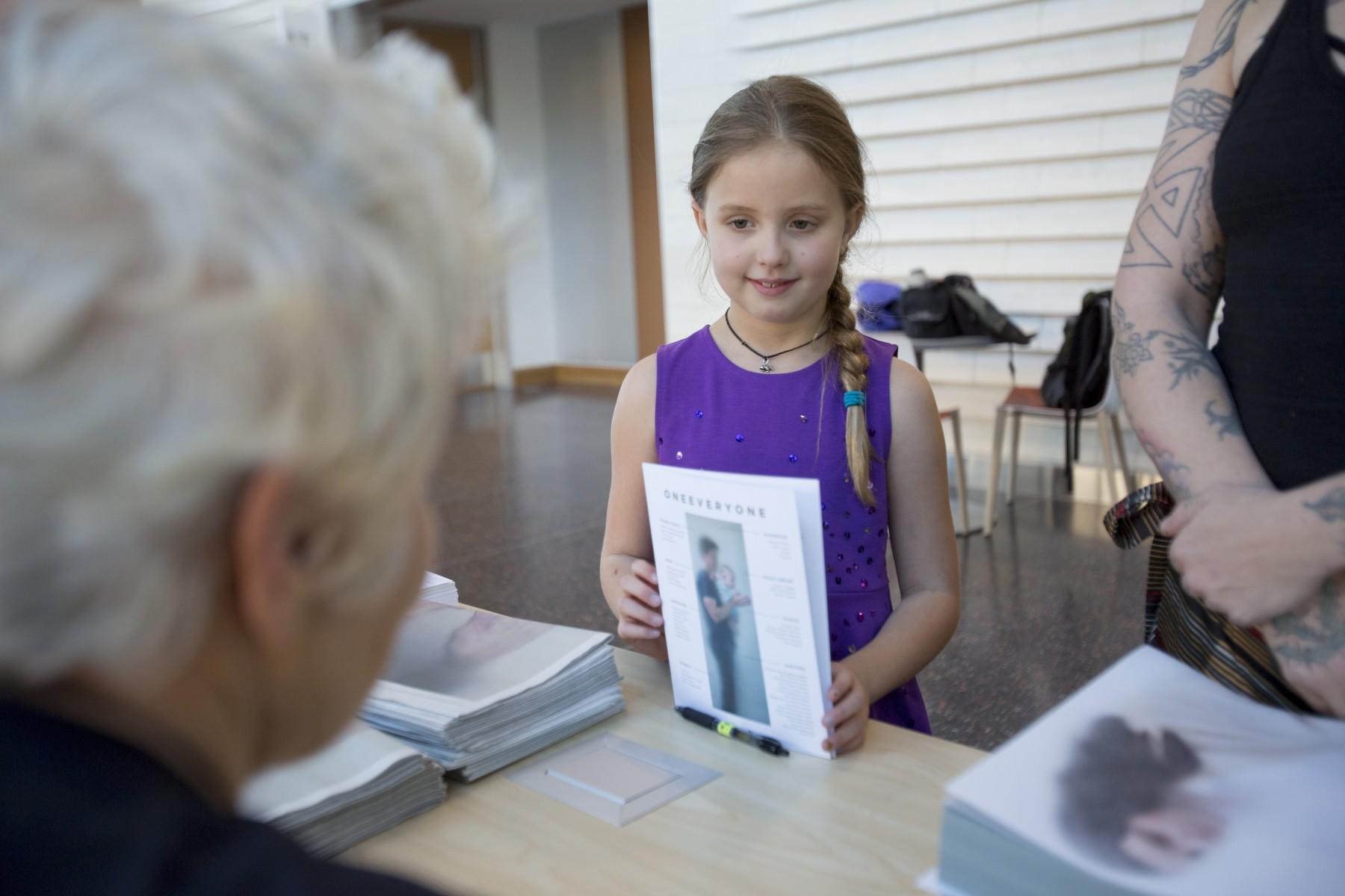 little girl holding pamphlet