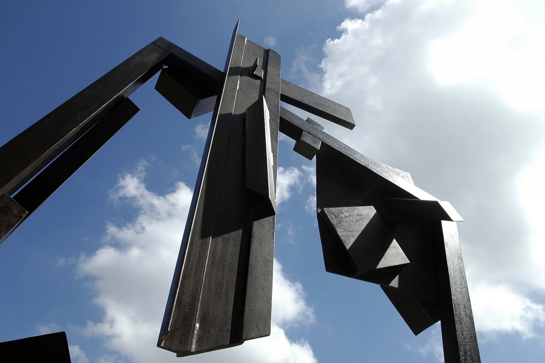 A view looking up at sculpture of steel with blue sky in background