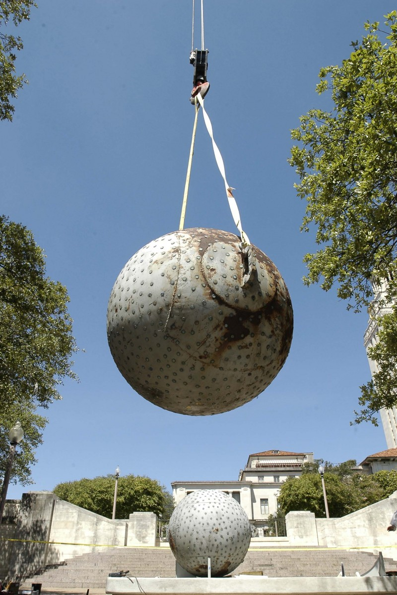 Giant sphere held in place in the air with crane ropes