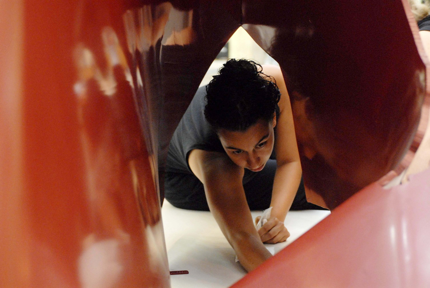 woman crawling inside tight space of red shiny sculpture