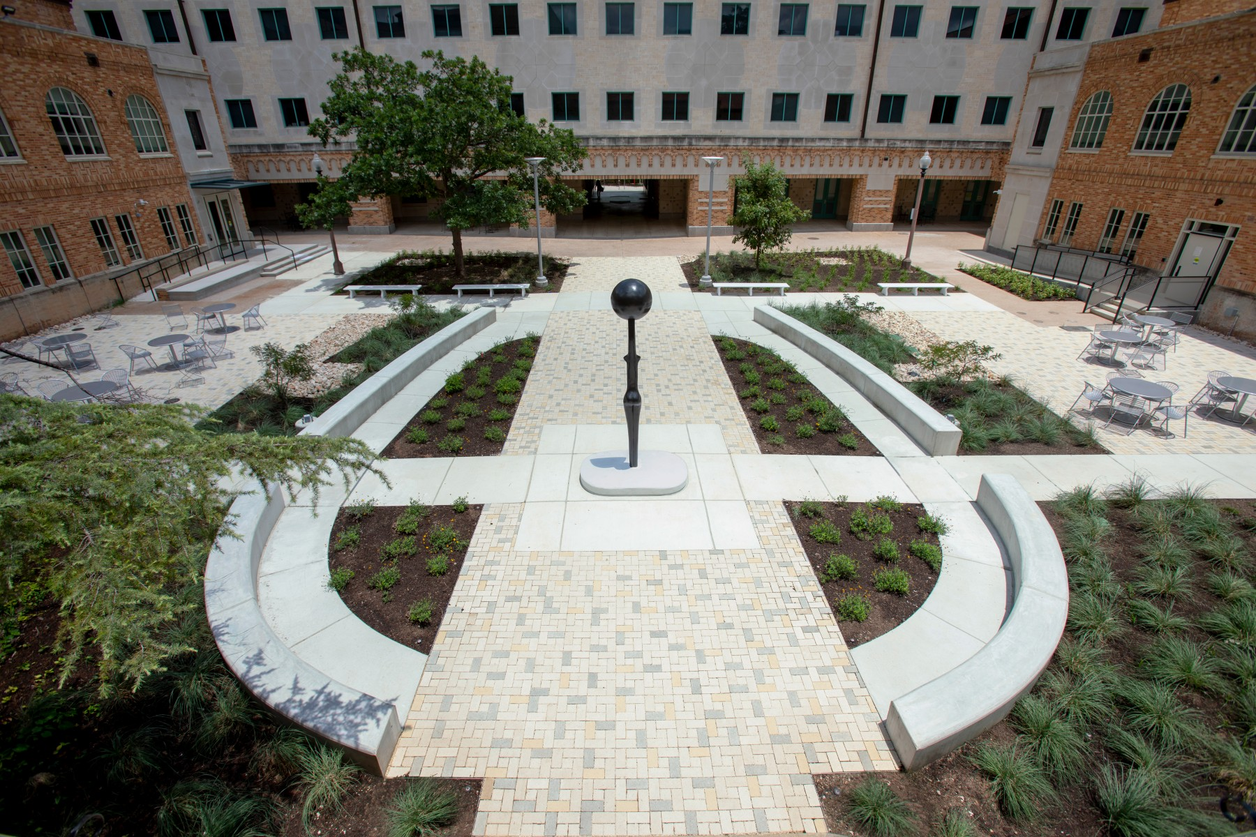 A wide angle image of Simone Leigh's Sentinel IV in the courtyard of Anna Hiss Gym. The building seems to surround the image and has a central staircase in the center of the image. The sculpture, a slender bronze figure with a bowllike head is placed in the center.