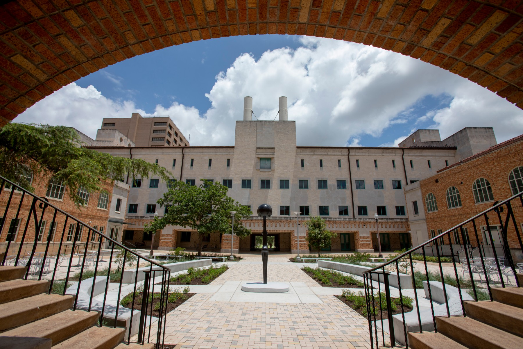 Sentinel IV, seen from behind. The work is centered in a landscaped courtyard. An apeture created by the building frames the work in this image with the circular ceiling coming down and two staircases framing the bottom edge.