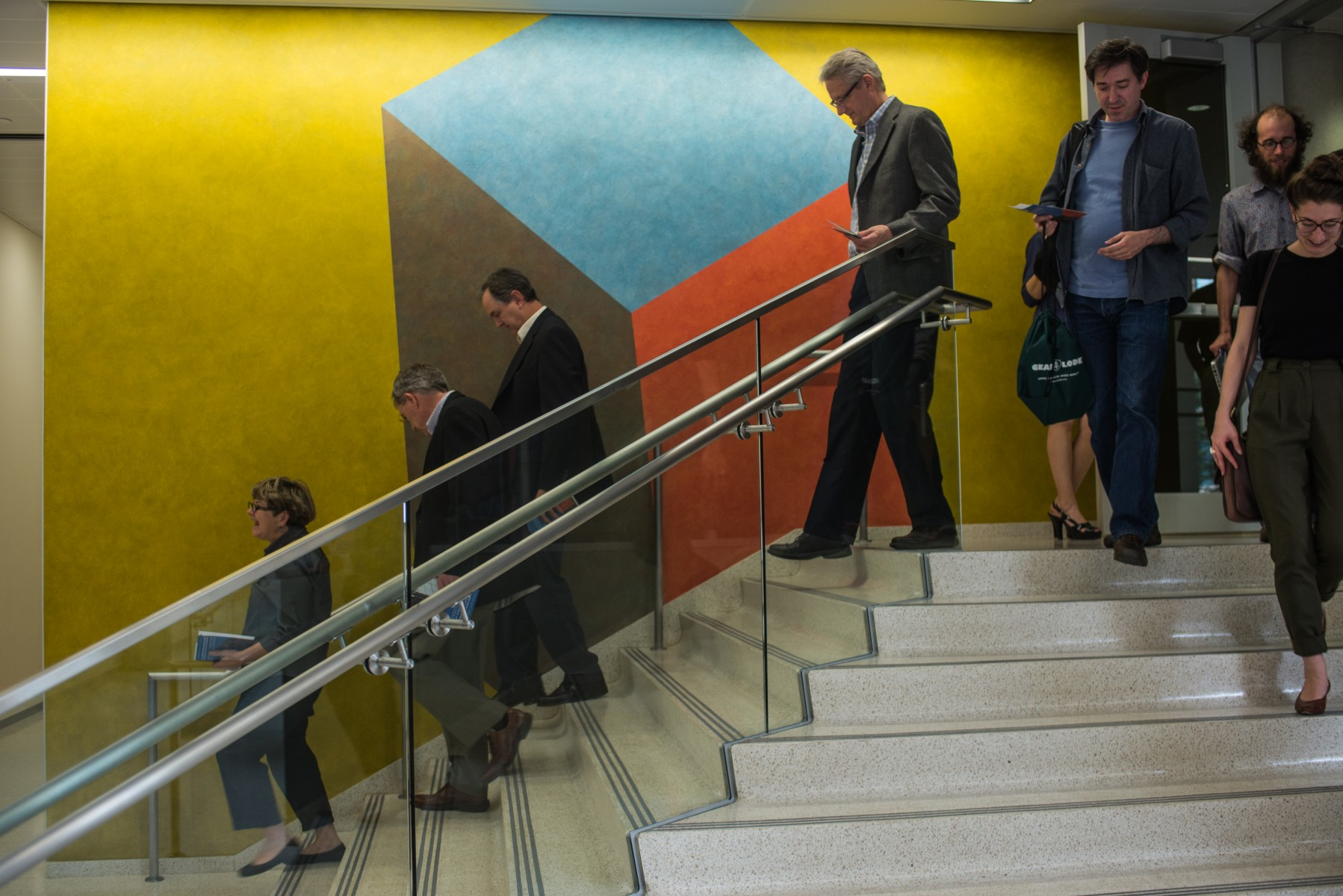 people walking down stairs in front of colored wall
