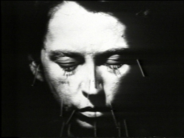 face closing eyes against black background