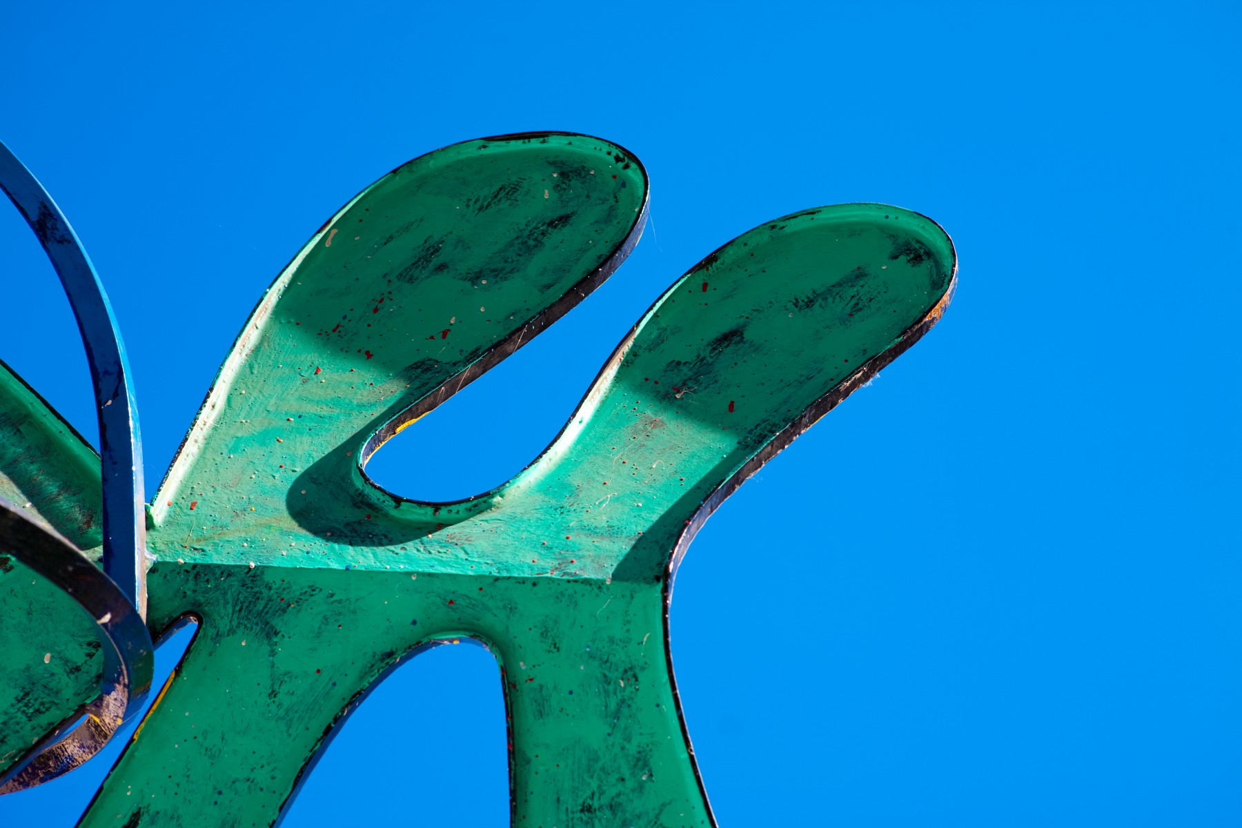Green curvy surface with blue sky in background