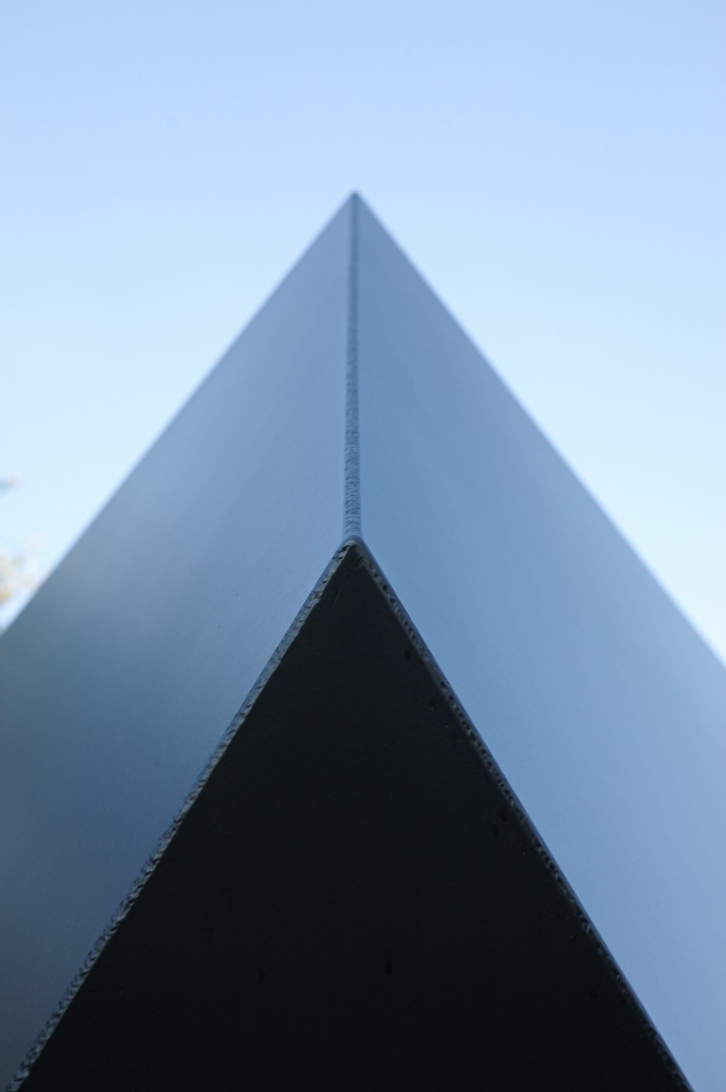 Black triangular shape pointed into middle top of frame with blue sky in background