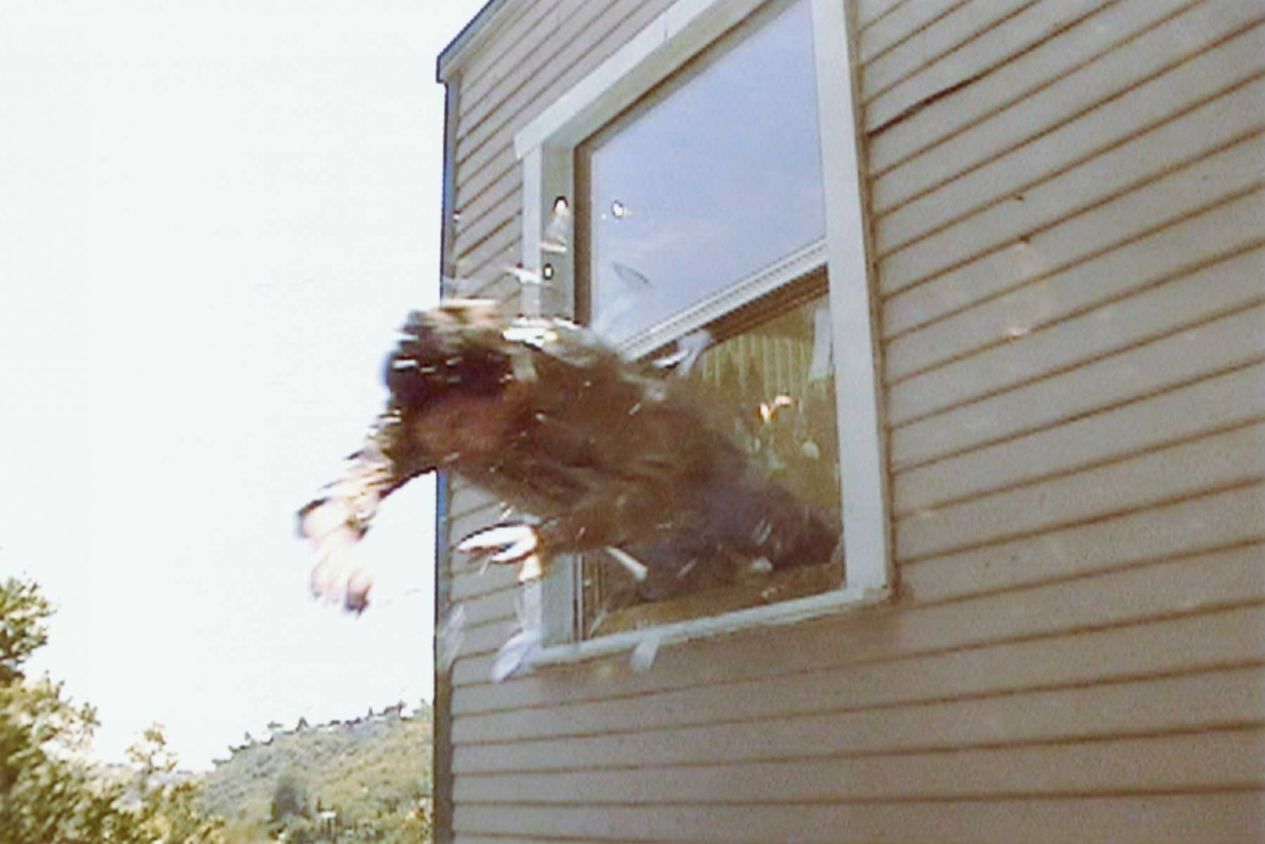 person midway jumping out of window of home