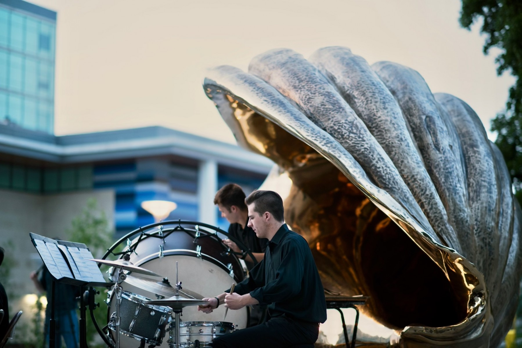 A drummer plays under the curve of Marc Quinn's