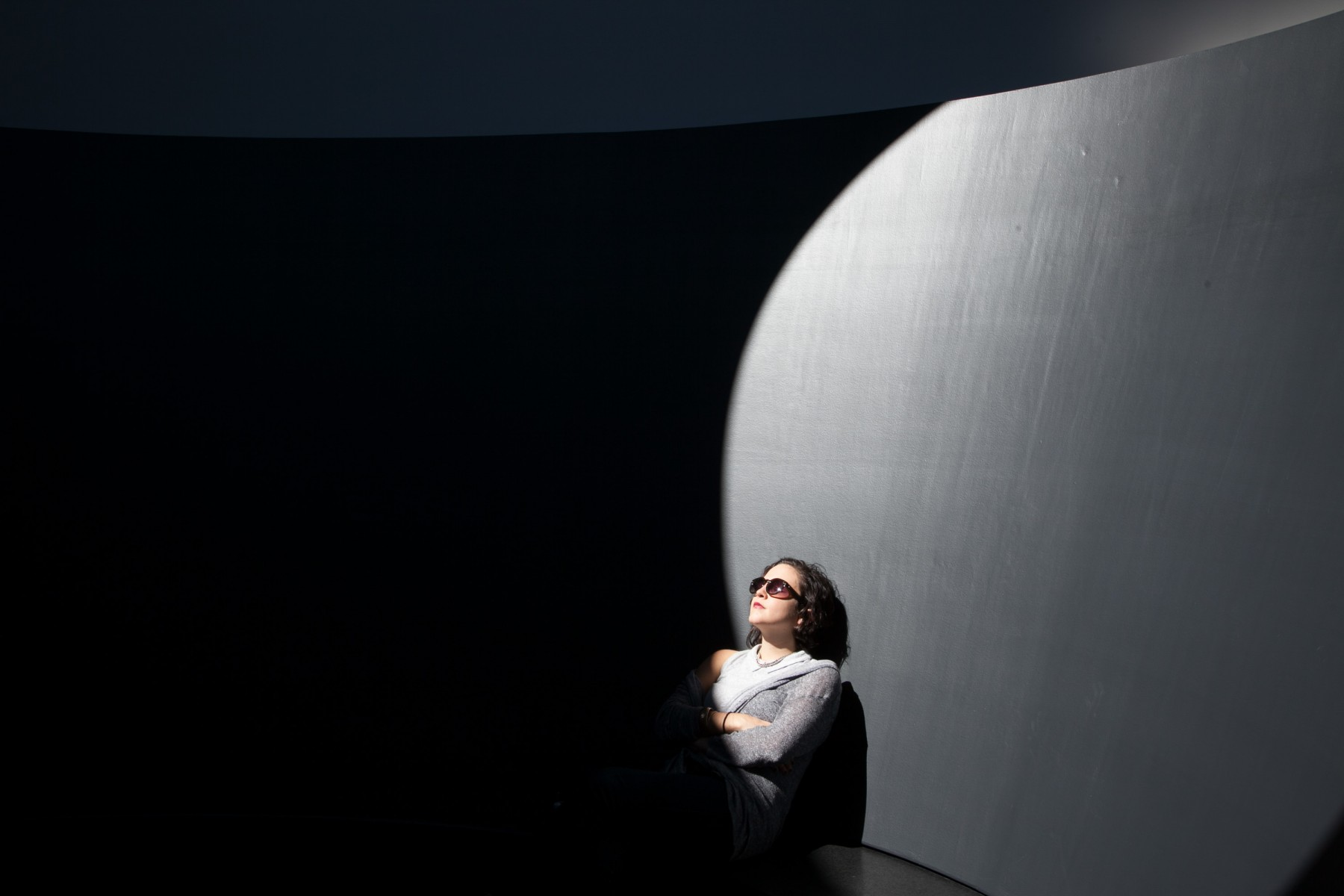 person sitting in sunlight looking up with sunglasses on