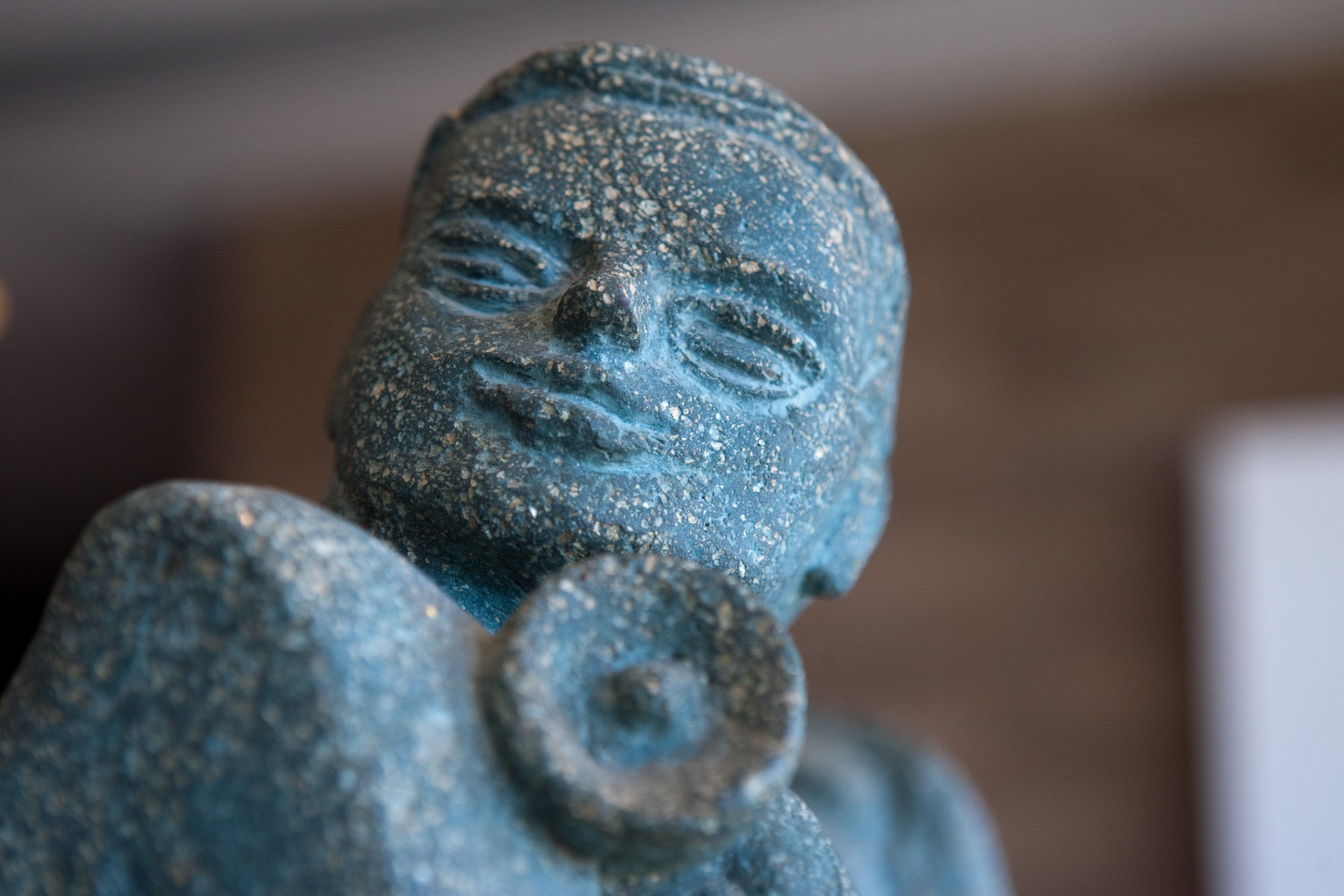 blue speckled face sculpture with blurry background