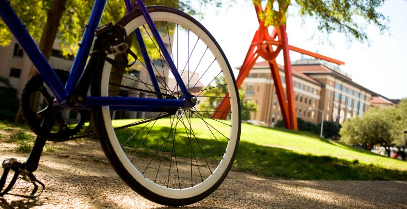 A bike wheel in front of a large red sculpture