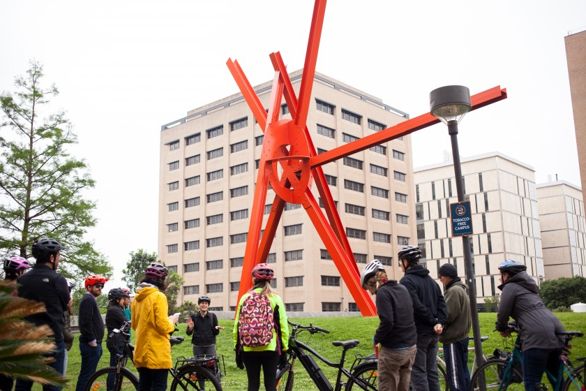 "Image of bike tour participants looking at ""Clock Knot"" by Mark Di Suvero"