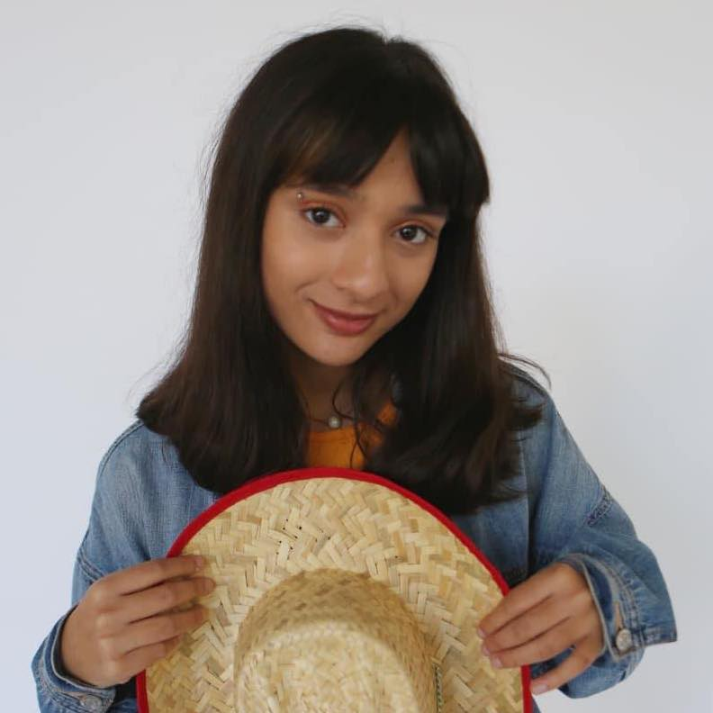 A headshot of Vega Shah. She has black hair and wears a denim shirt while holding a cowboy hat in the foreground of the photo